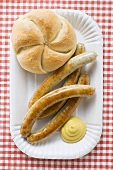 Sausages (bratwursts) with mustard & bread roll on paper plate