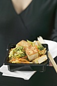 Fried tofu with vegetables, woman in background (Japan)