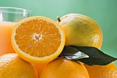 Several oranges, glass of orange juice in background