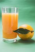 Glass of orange juice beside orange with leaf
