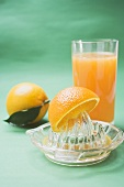 Glass of orange juice, oranges and citrus squeezer
