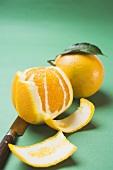 Zwei Orangen, geschält und ungeschält, mit Messer