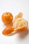 Zwei Clementinen (geschält und ungeschält)