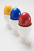 Three coloured eggs in egg cups