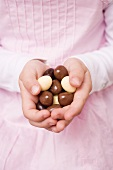 Child's hands holding chocolate eggs