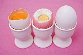 Three eggs in eggcups (raw & boiled with top cut off, whole)
