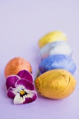 Chocolate eggs in foil, with pansy