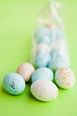 Pastel-coloured Easter eggs, some in cellophane bag
