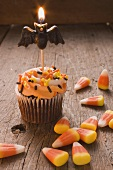 Cupcake with bat candle and candy corn for Halloween (USA)