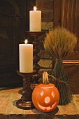 Autumn decorations: candles, cereal sheaf & pumpkin lantern