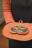 Hands holding Halloween biscuit with name on pot holder