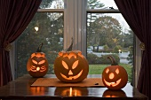 Pumpkin lanterns on table in front of window