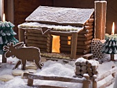 Gingerbread log cabin in snowy forest with gingerbread elk