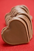 Chocolate hearts on red background