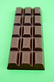 Bar of chocolate on green background