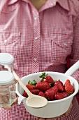 Frau hält Seiher mit Erdbeeren, Marmeladengläser und Kochlöffel