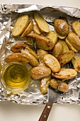 Rosemary potatoes on aluminium foil with spatula & olive oil