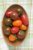 Different types of tomatoes in wooden dish (overhead view)