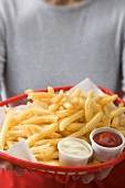 Woman holding basket of chips with ketchup and mayonnaise