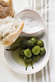Green olives in olive oil with salt and white bread