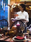 Table laid for Thanksgiving, woman serving sparkling wine (USA)