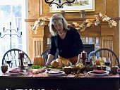 Woman serving stuffed turkey for Thanksgiving (USA)
