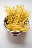Fusilli lunghi (long pasta spirals) in colander