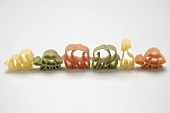 Coloured animal-shaped pasta in a row