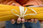 Child's hands holding a bundle of spaghetti