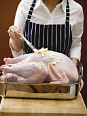 Woman brushing stuffed turkey with butter