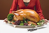 Woman holding platter with roast turkey and fruit