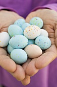 Hands holding chocolate eggs with pastel-coloured candy shells