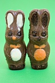 Two chocolate Easter Bunnies on green background