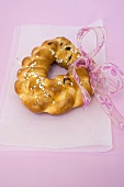 Plaited bread ring with pearl sugar and pink bow