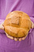 Hands holding round Easter bread