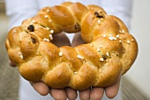 Hands holding plaited bread ring with pearl sugar (Easter)