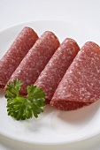 Four slices of salami with parsley on plate