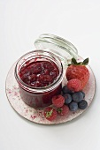 Jar of berry jam and fresh berries on plate