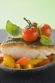 Fried fish fillet with peppers, tomatoes, basil