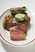 Beef steak with herb butter, bacon-wrapped beans & potatoes