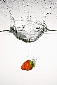 Strawberry falling into water