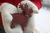 Hands in mittens holding two reindeer (Christmas decorations)