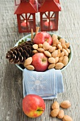 Red apples, almonds and cone in bowl in front of lanterns