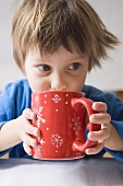 Child drinking out of large red mug