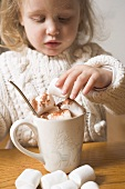 Small girl piling marshmallows on cup of cocoa