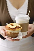 Woman holding muffin and cup of coffee