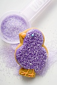 Easter biscuit (purple chick) and sugar for decorating