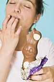 Woman holding chocolate Easter Bunny with a bite taken