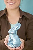 Woman holding chocolate Easter Bunny wrapped in foil
