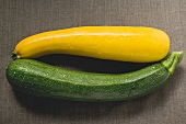 Yellow and green courgettes on brown fabric background